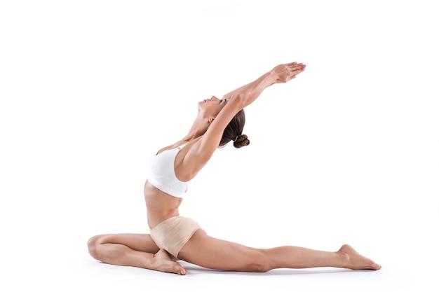 Красивая женщина упражнениями йоги представляют на белом фоне. концепция здорового образа жизни.