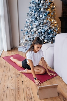 Bella donna che pratica yoga vicino alla finestra al mattino.