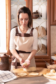Beautiful woman prepares pies in the kitchen of the house for her family. she holds the dough.