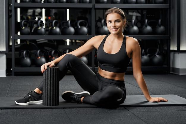マットの上でトレーニングの準備をしている美しい女性