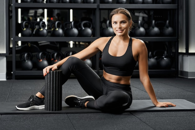 Beautiful woman preparing for workout on mat