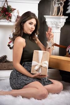 카메라에 포즈를 취하는 손에 앉아 아름 다운 여자