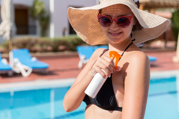 Beautiful woman protecting her skin against sunburn, applying sun lotion on her shoulder by the pool. sun protection factor in vacation, concept.
