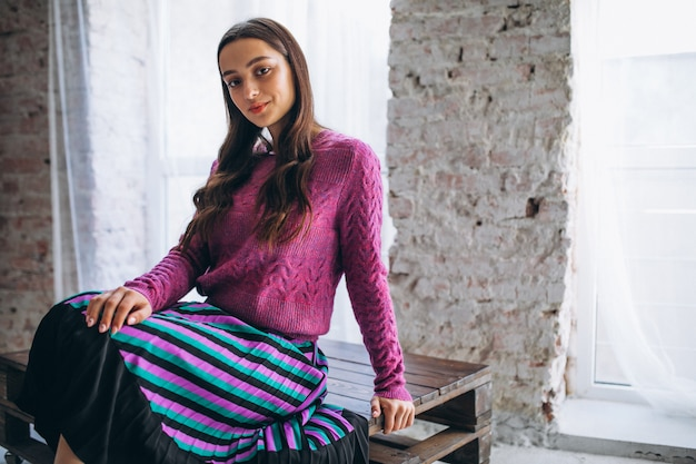 Beautiful woman in a purple sweater and skirt