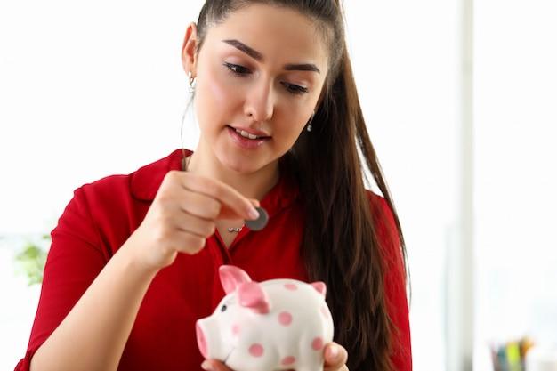 Красивая женщина кладет монету в керамическую копилку