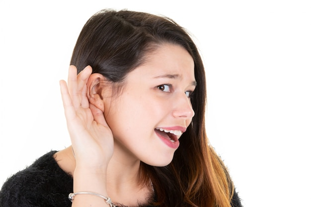 Beautiful woman puts hand to ear to hear better young girl listening something over white
