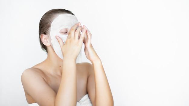 美しい女性は彼女の顔に化粧品のマスクを置く