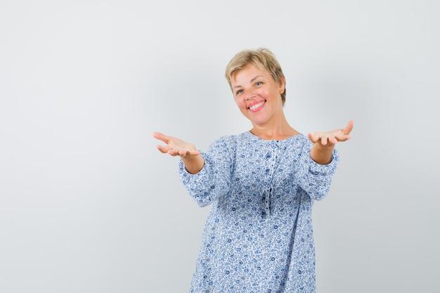 Bella donna che alza le mani per prendere qualcosa in camicetta fantasia e guardare felice, vista frontale.