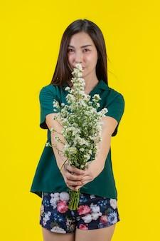 아름 다운 여자는 그녀의 손에 꽃을 밖으로 도달