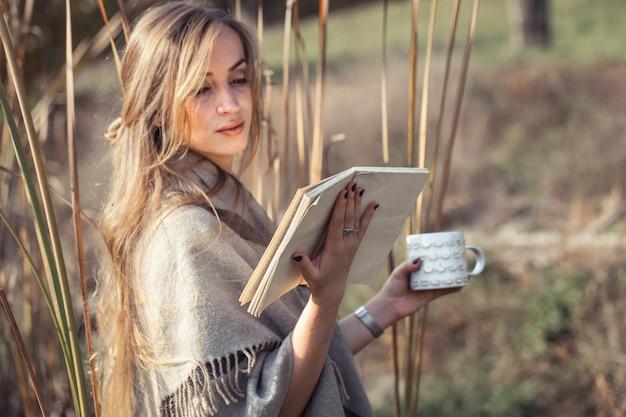 秋の森で本を読んで美しい女性