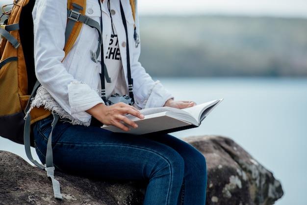 Beautiful woman reading book at mountain