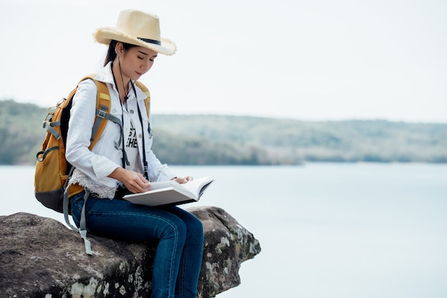 Beautiful woman reading book at mountain