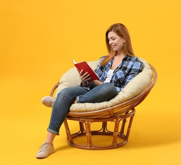 컬러 배경 안락의 자에 앉아있는 동안 책을 읽고 아름 다운 여자