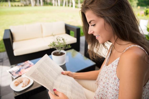 庭でニュースを読んで美しい女性