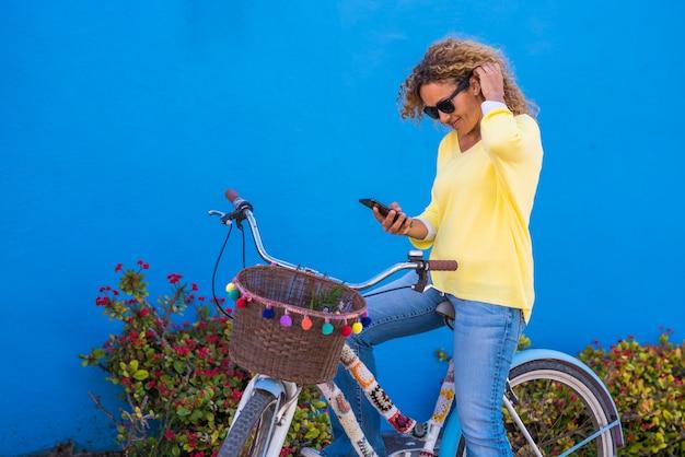 자전거에 앉아 있는 동안 휴대 전화에 문자 메시지를 읽는 아름 다운 여자. 젊은 백인 여성이 웃고 핸들바에 바구니를 들고 자전거에 앉아 스마트폰을 사용합니다.
