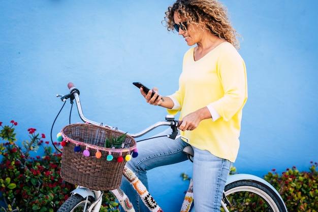 自転車に座って携帯電話でテキストメッセージを読んでいる美しい女性。笑顔とハンドルバーのバスケットと自転車に座ってスマートフォンを使用して若い白人女性