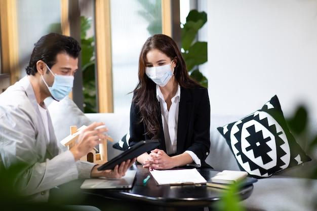 ハンサムな男性にオフィスのラップトップでオンラインプレゼンテーションを提供し、見せている美しい女性の不動産エージェント。フェイスマスク保護コロナウイルスを着用している人。
