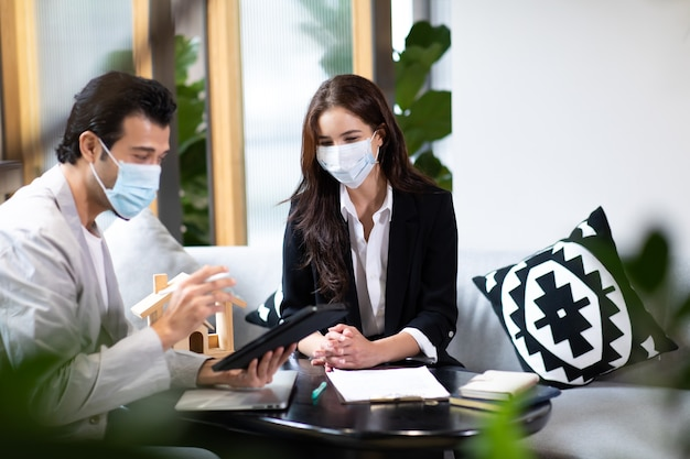 Beautiful woman real estate agent offering and showing online presentation on laptop in office to handsome man. people wearing face mask protective corona virus.