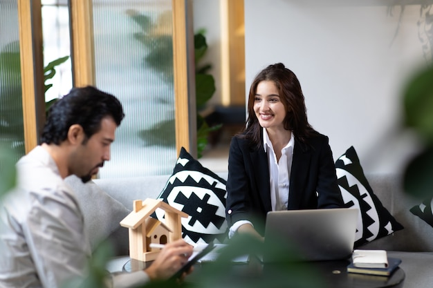 Beautiful woman real estate agent offering and showing online presentation on laptop in office to handsome man.