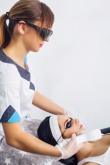Красивая женщина, получающая процедуру лазерной эпиляции
