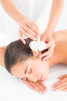 Beautiful woman receiving ear candle treatment at spa center