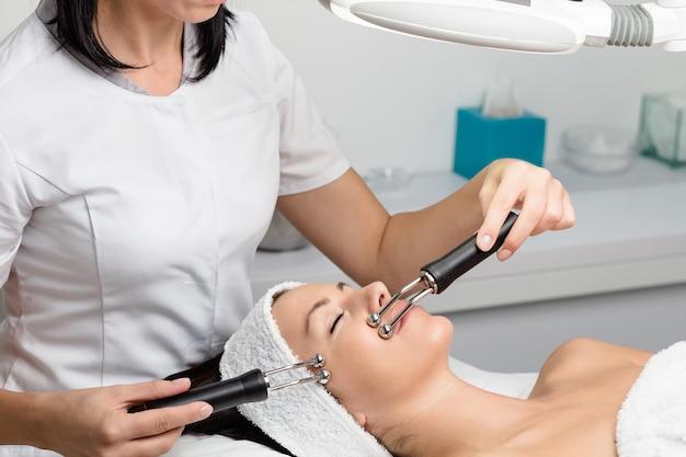スパサロンで顔の微小電流治療を受けている美しい女性。顔の手技に電気インパルスを使用する美容師。