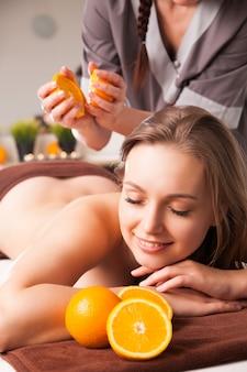 Красивая женщина, получающая спа-процедуры с апельсинами в спа-салоне