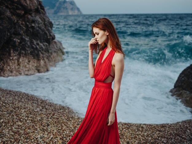 Beautiful woman in red dress beach ocean landscape waves.