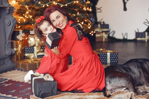 Beautiful woman in a red dress. family at home. mother with daughter. people with a dog.