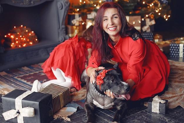 Bella donna in un vestito rosso. famiglia a casa. madre con figlia. persone con un cane.
