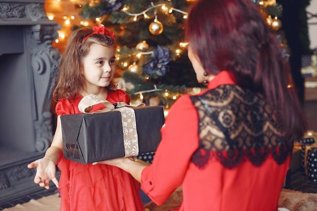 Bella donna in un vestito rosso. famiglia a casa. madre con figlia.