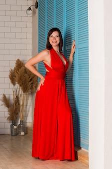 Beautiful woman in red dress in interior, sensual portrait