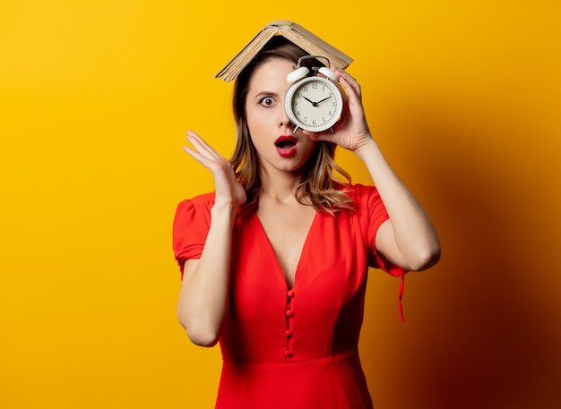 Beautiful woman in red dress with alarm clock