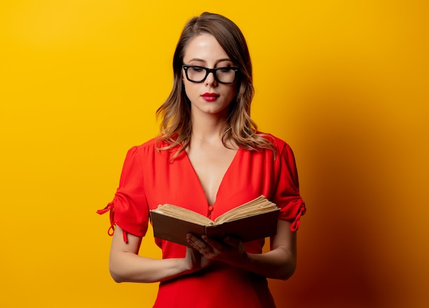 Beautiful woman in red dress with book on yellow wall