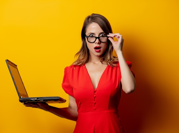 Beautiful woman in red dress with laptop computer on yellow wall