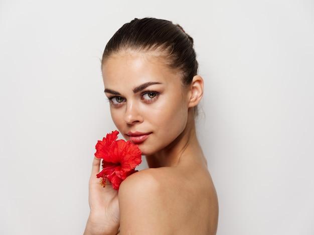 美しい女性赤い花きれいな肌モデルトリミングビュー