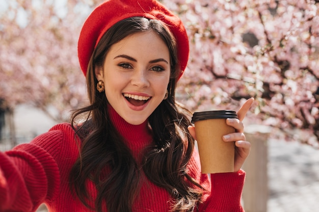 Beautiful woman in red outfit holds glass of tea and takes selfie on background of sakura. portrait of brunette girl in hat smilimg and posing with coffee cup