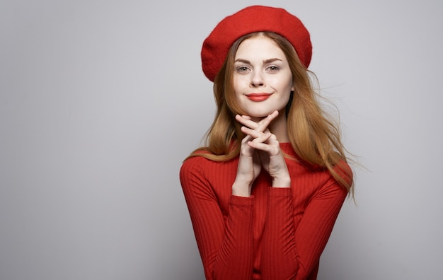 Beautiful woman in red sweater and hat cosmetics model gray wall.