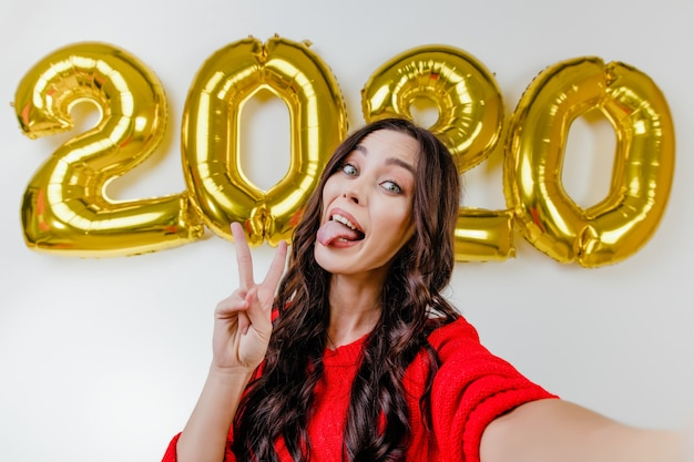 Beautiful woman in red sweater making funny selfie in front of 2020 new year balloons