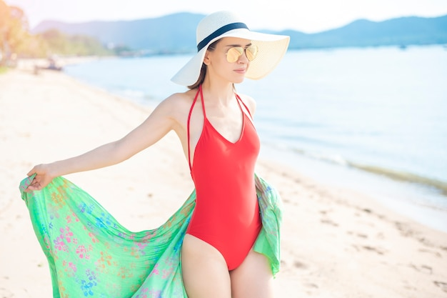 Beautiful woman in red swimsuit is relaxing on the beach, summer concept