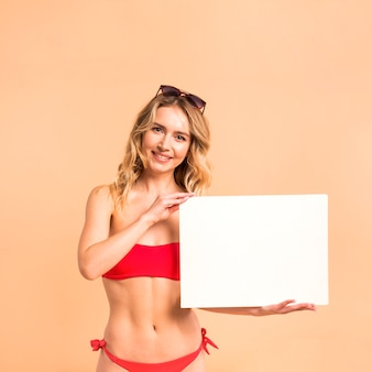 Beautiful woman in red swimsuit showing blank paper