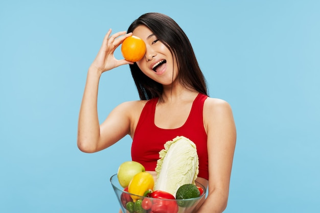 Beautiful woman in a red tank top with fresh vegetables and fruits