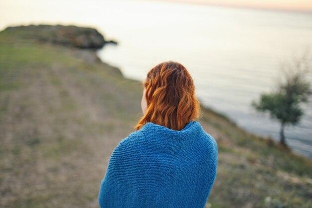 美しい女性の金髪の女性は、自然風景旅行の後ろ姿を賞賛します