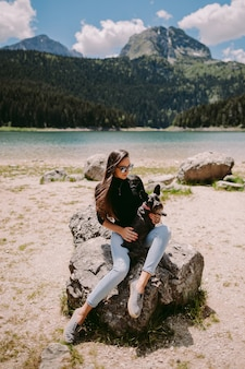Beautiful woman relax in mountains and lake view. female model posing and relax in mountains