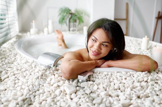 美しい女性、ミルク風呂でリラックス。バスタブの女性、スパの美容とヘルスケア、バスルームのウェルネストリートメント、背景の小石とキャンドル