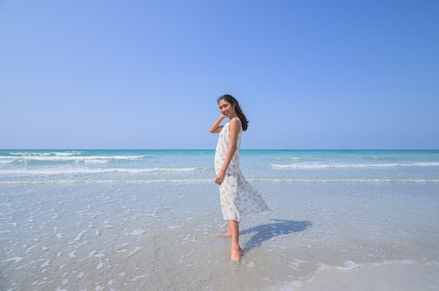 A beautiful woman in a relaxed white dress and enjoys the beach in the daytime.