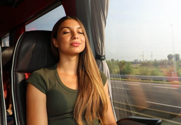 リラックスして、快適なバスに座って寝ている美しい女性。バスまたは電車の乗客が座席に座って寝ている。
