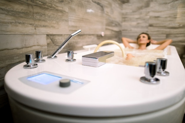 Beautiful woman relaxing in the bathtub having a hydromassage therapy. focus on the bath