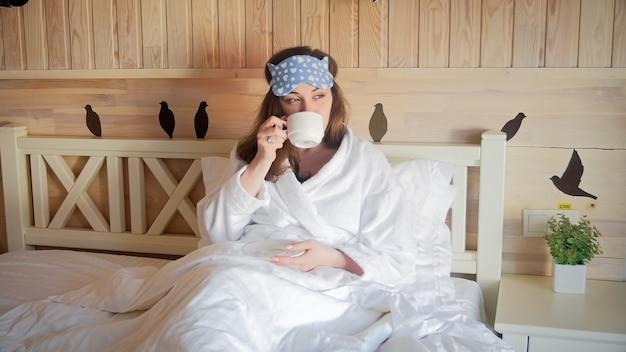 Красивая женщина расслабляющий в постели, пить кофе утром