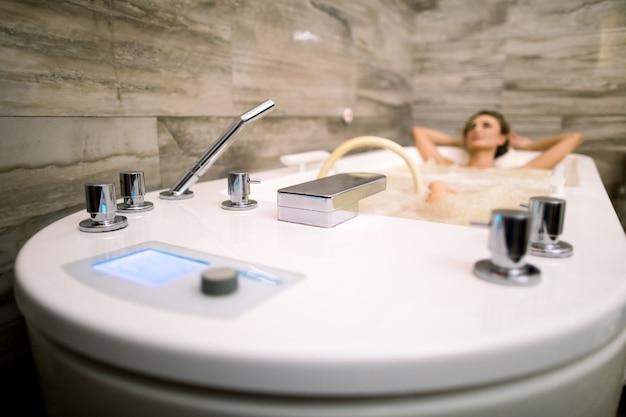 ハイドロマッサージ療法を備えたバスタブでリラックスした美しい女性。お風呂に集中